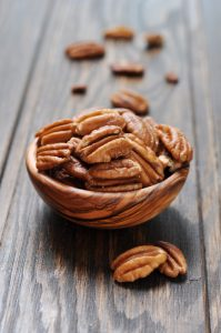 Pecan nuts in a wooden bowl closeup on wooden background
